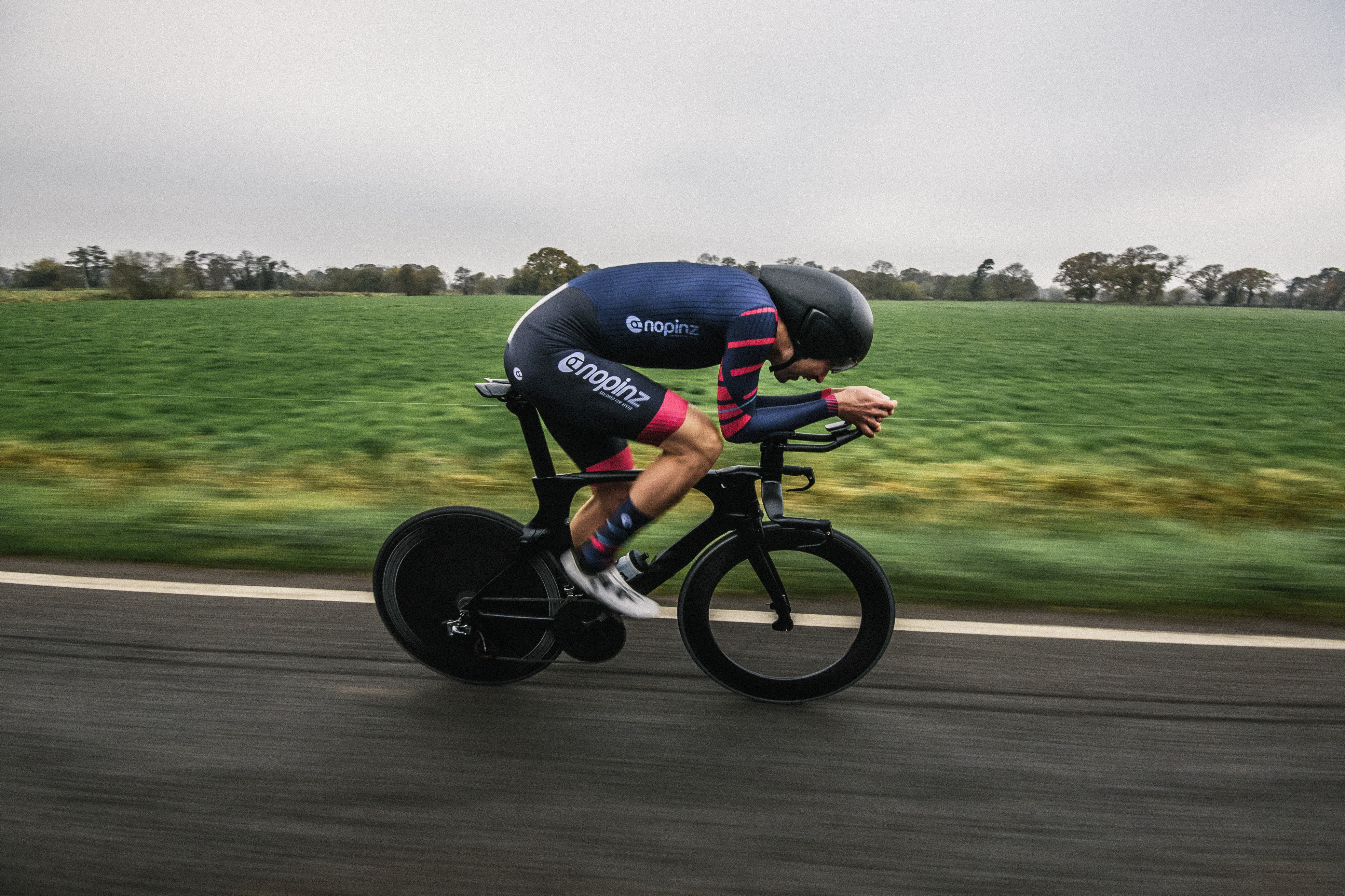 Cyclist rides a time trial bike wearing a Nopinz skinsuit
